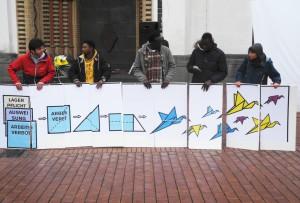 Menschen halten Transparent, mit Bild: Dokumente zu Ausweisung und Arbeitsverbot werden zu Vögeln gefaltet