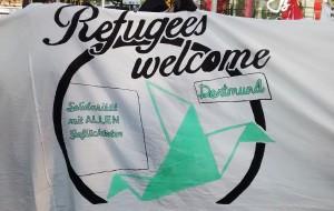 Banner Refugees Welcome Schriftzug und stilisierter gefalteter Kranich